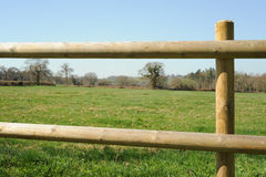 Post and rail Fence. Photograph of a post and rail fence with a field in the background Stock Photo
