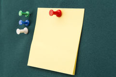 Post-it with red pushpin. Yellow post-it note with red pushpin on a green board Stock Photos