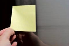 Post-it on refrigerator door. Man removes blank post-it out of refrigerator door Stock Images