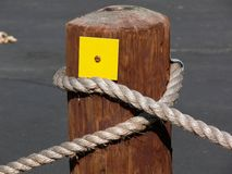 Post On A Rope. Wooden parking post with length of rope wrapped around it. And a square yellow thing Stock Images