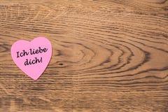 Post-it rosado del corazón con el texto 'dich del liebe de Ich 'en un fondo de madera Traducci?n: ?Te amo ? ilustración del vector