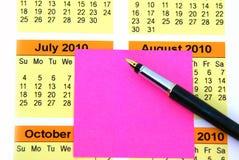 Post-it rosado en calendario Fotografía de archivo libre de regalías