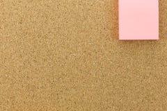 Post-it rosado en tablero del corcho Fotografía de archivo