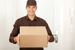 Post shipping. Handsome masculine postman in brown formal clothes shipping deliver a cardbox cartoon
