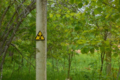 Post with the sign of radiation at an abandoned military base in the woods Royalty Free Stock Images