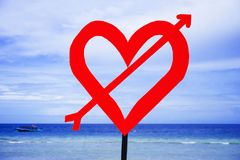 post signal with red love heart and arrow at beach on a blue sea and sky background in Valentines day and romance concept. Post signal with red love heart and Royalty Free Stock Photos