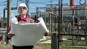 Post technische directeur met werkende tekeningen bij kernenergiepost stock footage