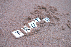 Post Truth. Letters spelling `truth` becoming buried in sand, depicting the Oxford English Dictionary`s word of 2016 royalty free stock photo