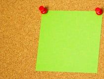 Post-it verde en un fondo del coarkboard Imagen de archivo