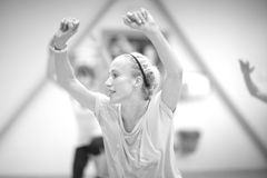 Post-workout stretches. Young spirited woman having workout session in the gym, monochrome Stock Photo