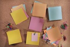 Post-it y materiales de oficina en blanco adaptables en tablero de mensajes del corcho Imagen de archivo libre de regalías