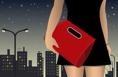 Postać dziewczyna w sukni z czerwoną torbą na tle nocy miasto Fotografia Royalty Free