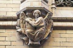 Postać trzyma książkę kamienny anioł na fasadzie budynek, Hiszpania zdjęcie royalty free