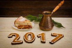 Postać w 2017 miodownik, świeczki, jabłczany kulebiak, garnki i świerczyna, kapuje na drewnianym tle Obrazy Stock