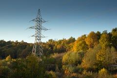 Posta ad alta tensione al backg ad alta tensione del cielo della torre della foresta di autunno Immagine Stock