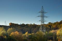 Posta ad alta tensione al backg ad alta tensione del cielo della torre della foresta di autunno Fotografia Stock