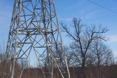 Posta ad alta tensione al backg ad alta tensione del cielo della torre della foresta di inverno Fotografia Stock