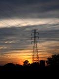 Posta ad alta tensione al tramonto. Fotografia Stock