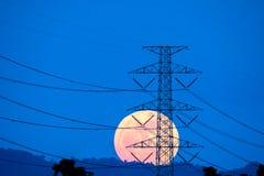 Posta ad alta tensione con la luna piena Fotografia Stock