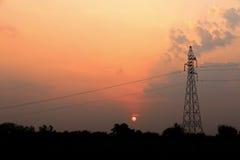 posta ad alta tensione di elettricità con i cavi su penombra e sull'albero s Immagini Stock