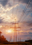 Posta ad alta tensione, fondo ad alta tensione di tramonto del cielo della torre Fotografia Stock