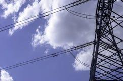 Posta ad alta tensione sotto in cielo nuvoloso blu Immagine Stock Libera da Diritti