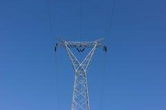 Posta ad alta tensione, torre del trasporto di energia contro cielo blu Immagine Stock Libera da Diritti