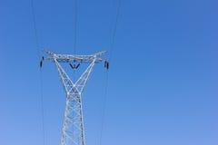 Posta ad alta tensione, torre del trasporto di energia contro cielo blu Fotografia Stock Libera da Diritti