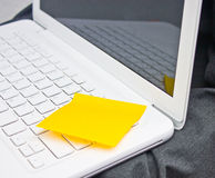 Posta appiccicosa gialla della nota sul computer portatile bianco. Fotografia Stock Libera da Diritti