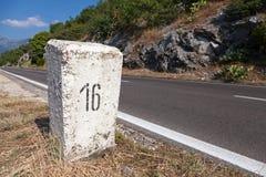 Posta bianca della pietra di chilometro sul bordo della strada immagine stock