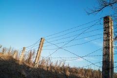 Posta con filo spinato contro il cielo Fotografie Stock Libere da Diritti