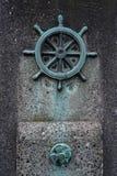 Posta concreta con la ruota nautica d'ottone fotografia stock