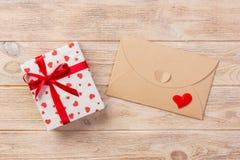 Posta della busta con la scatola rossa di regalo e del cuore sopra fondo di legno arancio Concetto di saluto di Valentine Day Car immagini stock