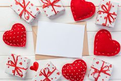 Posta della busta con la scatola rossa di regalo e del cuore sopra fondo di legno bianco Concetto di saluto di Valentine Day Card immagine stock