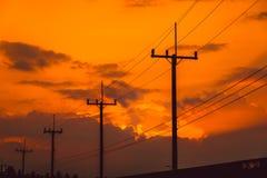 Posta di elettricità della siluetta con il bello tramonto Immagine Stock