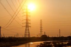 Posta di elettricità della siluetta sul tramonto Fotografia Stock