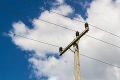 Posta di elettricità sul fondo del cielo blu Immagine Stock