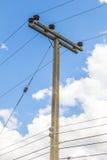 Posta di elettricità sul fondo del cielo blu Fotografia Stock