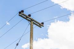 Posta di elettricità sul fondo del cielo blu Fotografie Stock