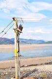 Posta di elettricità sulle rive del fiume di Mawddach in Galles, Regno Unito Fotografia Stock