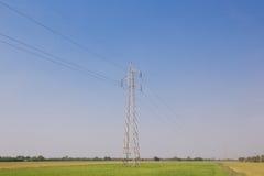 Posta o torre ad alta tensione di alta tensione nel campo verde Fotografie Stock Libere da Diritti