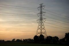 Posta o torre ad alta tensione di alta tensione nel giacimento del riso, alba Immagine Stock Libera da Diritti
