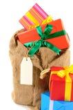 Posta påsen eller strumpan som fylls med julgåvor som isoleras på vit bakgrund Arkivfoto