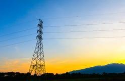 Posta, piloni di elettricità e linee ad alta tensione al tramonto Immagini Stock