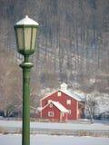 Posta verde della lampada e granaio rosso coperti in neve fotografie stock libere da diritti