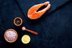Posta vermelha crua Peiece de salmões frescos na placa de corte perto do sal do mar, pimenta, fatias do limão no fundo preto cobr Imagens de Stock
