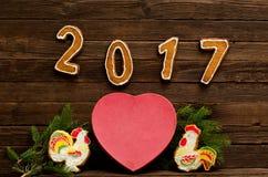 Postacie 2017 na ciemnym drewnianym tle, dużym sercu, dwa miodowników kogucie i świerczynie, rozgałęziają się Obraz Royalty Free