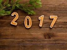 Postacie 2017 na drewnianym tle pod jodły gałąź przy wierzchołkiem rama, Zdjęcie Stock