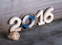 Postacie 2016 na starym popielatym drewnianym tle w morze stylu z zalecają się Zdjęcie Royalty Free