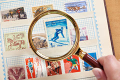 Postage sport stamp with skier under magnifier on album. Close-up Stock Photo